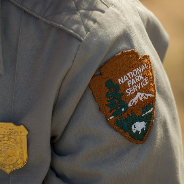 a NPS badge and patch on a ranger uniform
