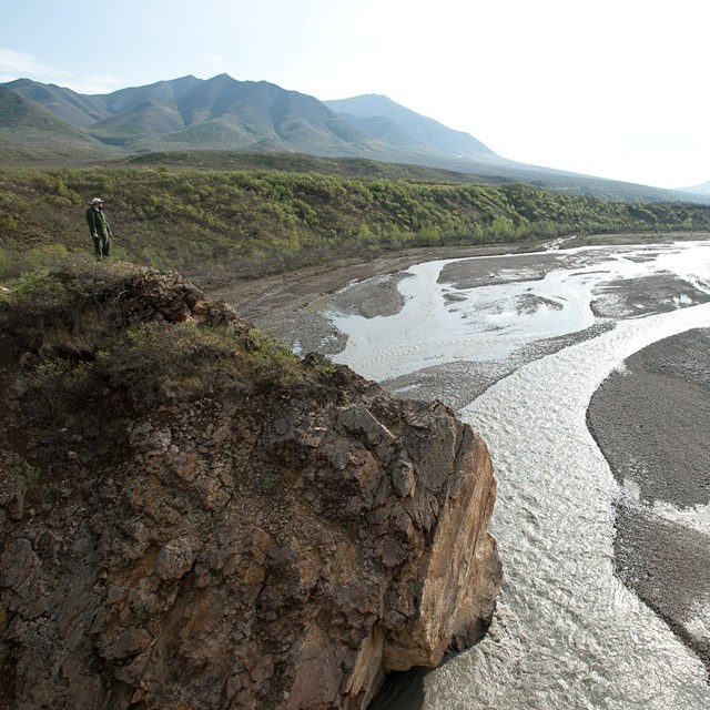 person standing on a bluff overlooking a wide braided river