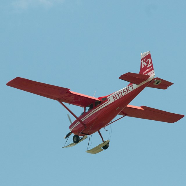 a red plane flying through a blue sky