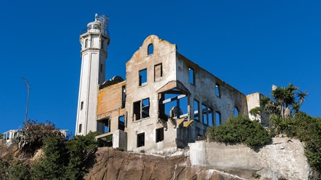 Tall lighthouse and silhouette of ruined building sit atop a cliff.