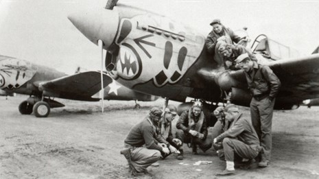 Men play a game on the ground near an airplane