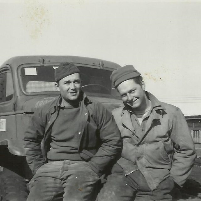 two men sit on the bumper of a truck