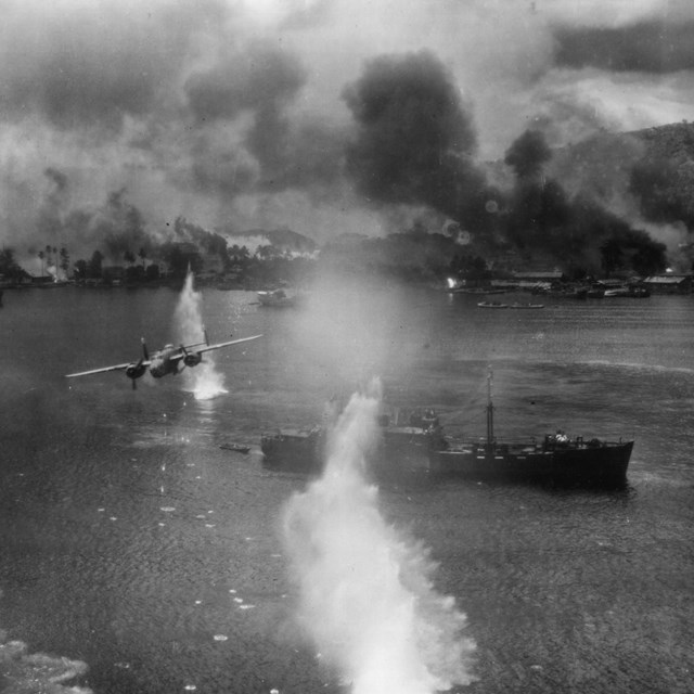 Plane flying over battleship with things exploding