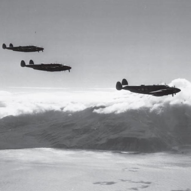 Black and white photo of three planes flying over ocean and mountains