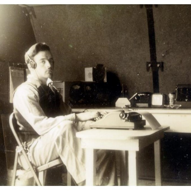 Black and white photo of man seated at typewriter, wearing radio headset, in an office.