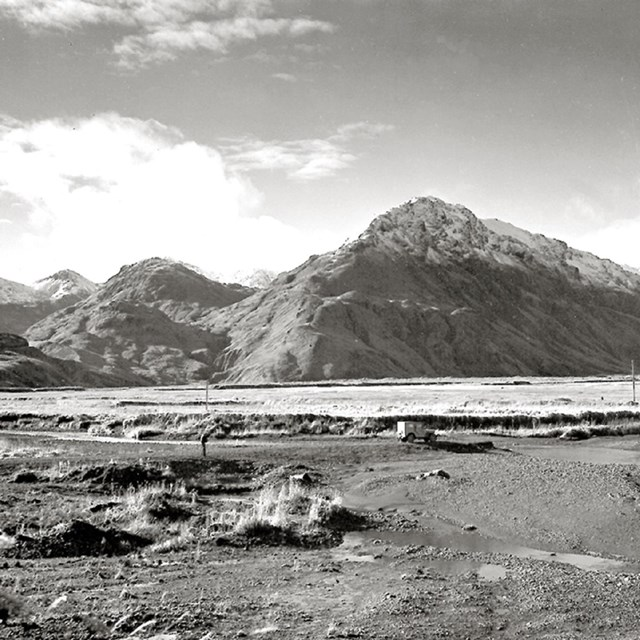 Black and white landscape photo of mountains and water.