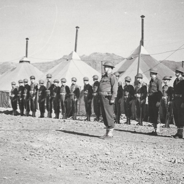 Sepia-toned photo of men in uniform in front of tents, on parade ground.