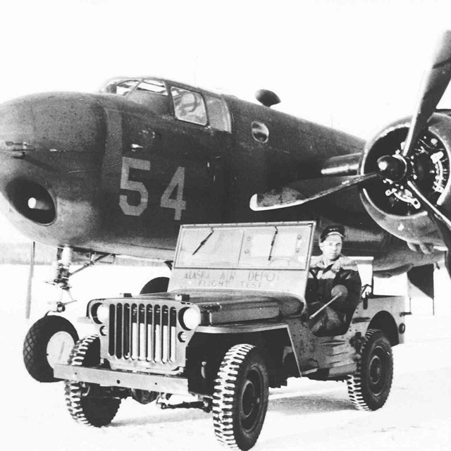 Black and white photo of B25 airplane and jeep with man in it.