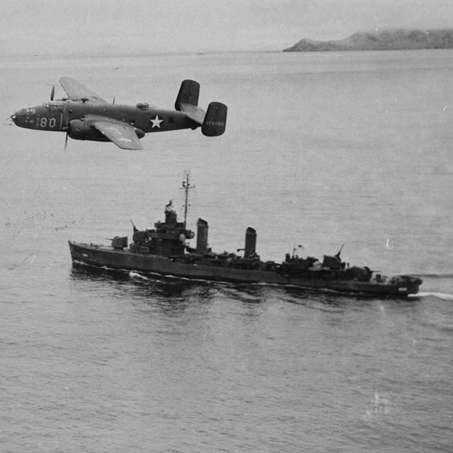plane flying over a world war two era ship