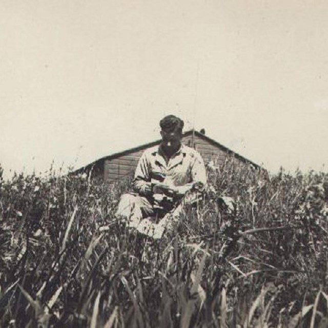 Man reading letter in meadow, with wooden building and sky in background.