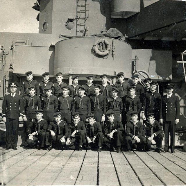 Three rows of uniformed sailors in front of a submarine