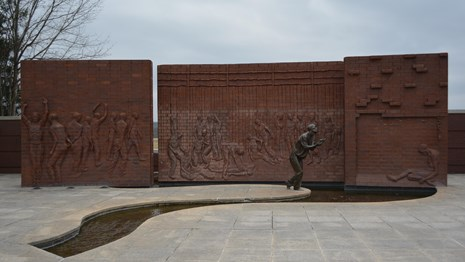 A courtyard with a large wall sculpture and statue of prisoners of war