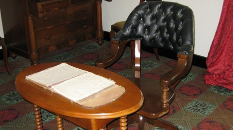 A leather chair pulled up to a wooden table with documents spread out on top.