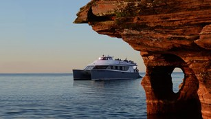 A large catamaran tour boat travels around an overhanging sandstone cliff at sunset.