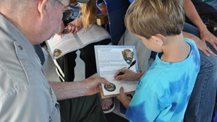 Young child signing a certificate with a park ranger.