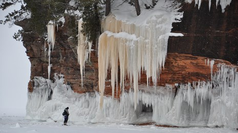 A lone person stands on a frozen lake looking at an ice-covered, sandstone cliff.