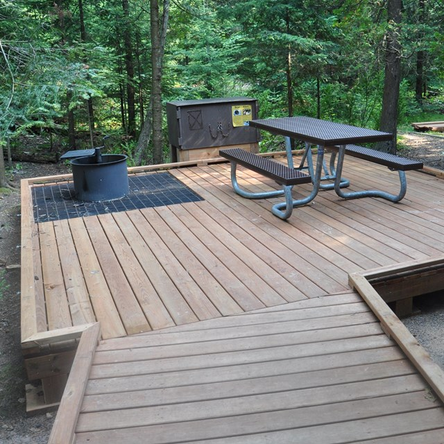 Raised wide boardwalk at campsite with accessible picnic table, bear box, and fire pit.