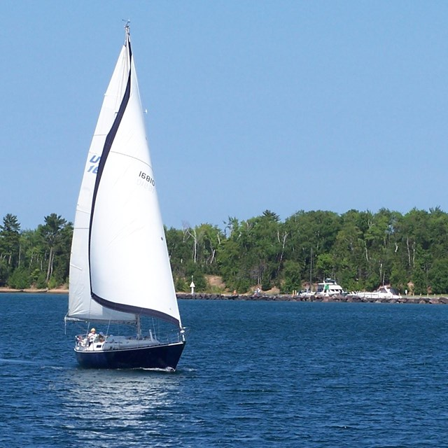 Sail boat with sails up on a body of water with land in background.