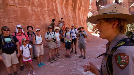 a ranger speaks to a group of people in front of a rock wall