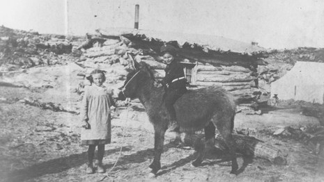 Little girl holding donkey with a boy on its back in front of historic Wolfe Cabin.