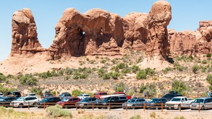 cars crowded into parking spaces below towering sandstone features