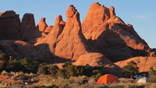 an orange tent sits beneath high red rock walls