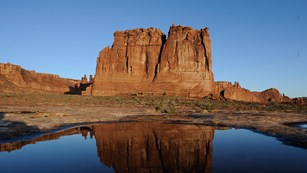 A giant rock monolith reflected in a still pool of water in the foreground