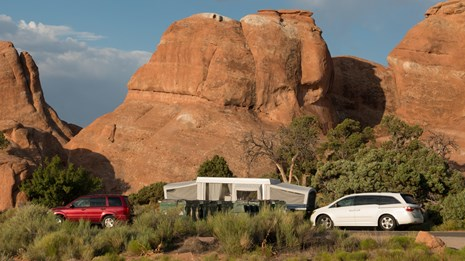a pop-up trailer and two vehicles in front of red rock cliffs