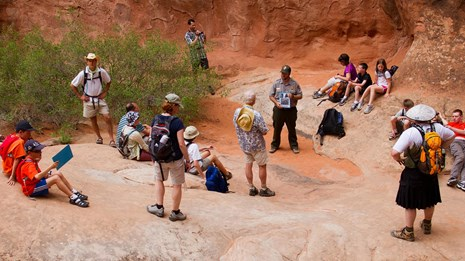 a group of people in surrounded by red rock walls