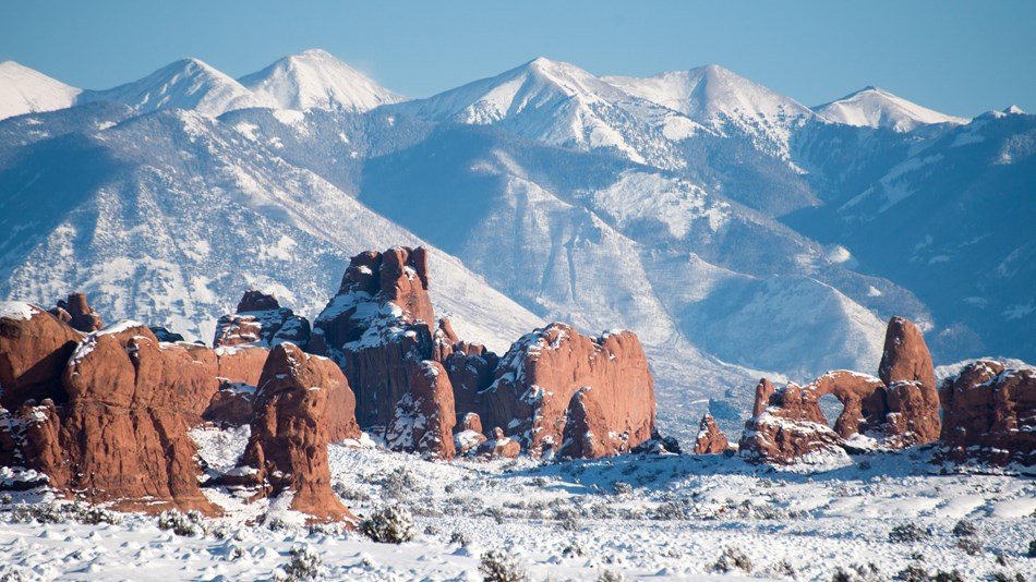 snow-dusted redrock arch, pinnacles, with mountains in the background