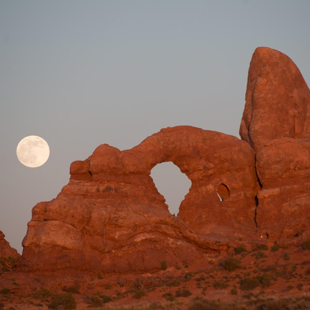 a large red rock arch with the rising full moon in the background