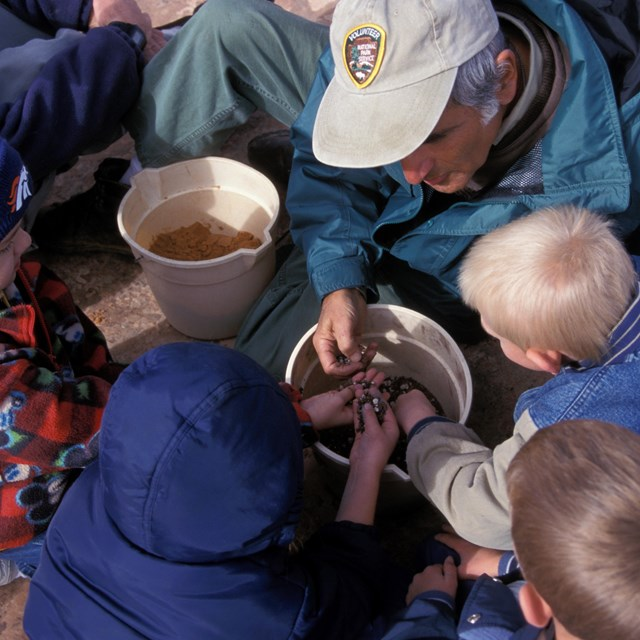 children reach into a pail of gravel