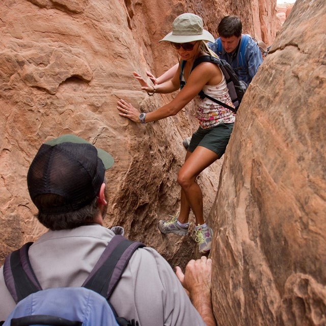two people scramble through a narrow gap in the rocks
