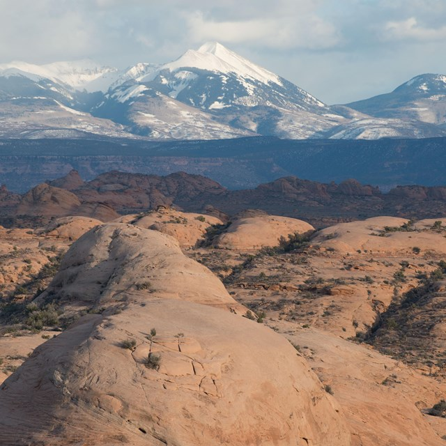 rolling brown rocky slopes with snow-capped mountains in the distance