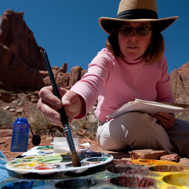 A woman dips a brush into a palette of paints