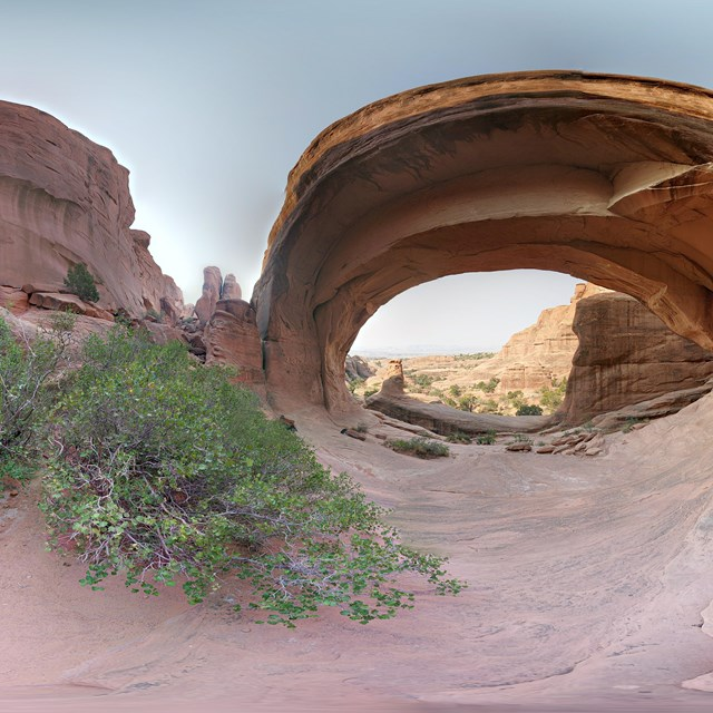 a panoramic image of a broad, stone arch