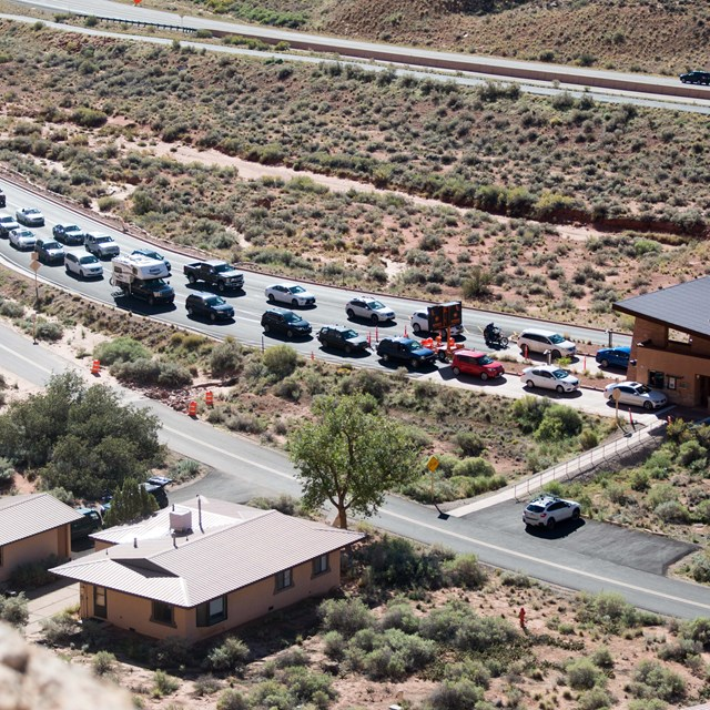 a line of cars in front of a small building