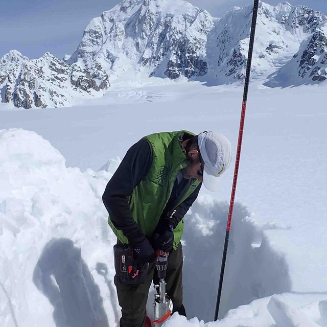 A researcher measures snow depth.