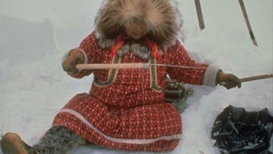 A woman ice fishing in traditional Arctic clothing.