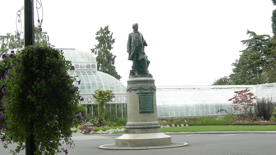 Image of large stature and pedestal in garden area.