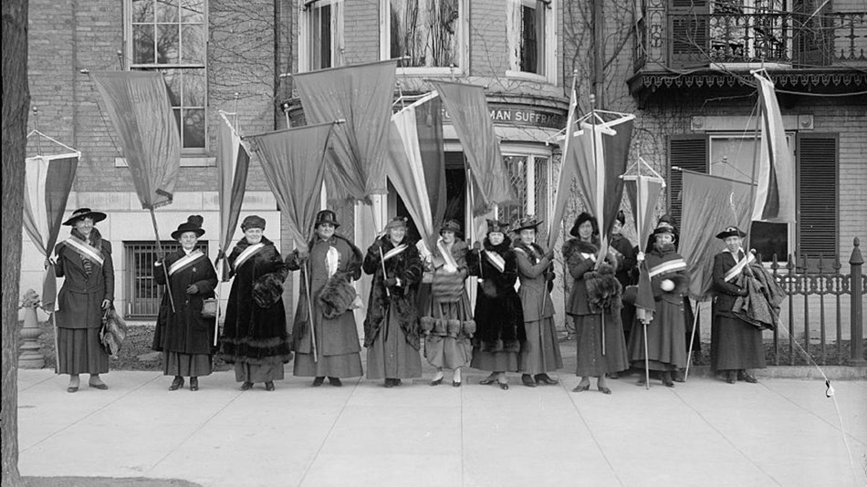 A group of suffragists standing with banner and flags in front of a building. Library of Congress.