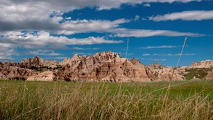 looking up from prairie grasses, jagged badlands buttes stretch into a cloudy blue sky