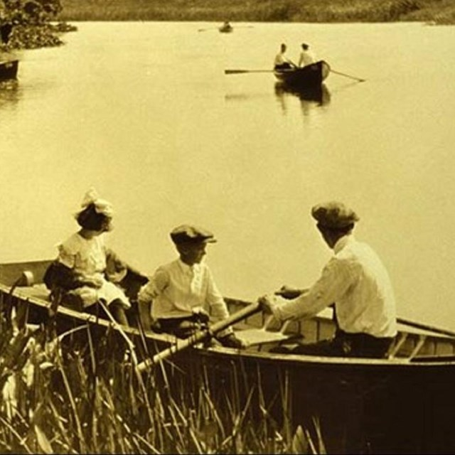 Photo of adult and t children in a boat on a pond.