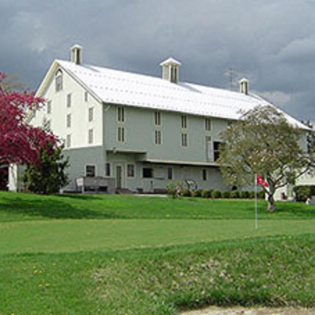 Photo of a white house in a green meadow.