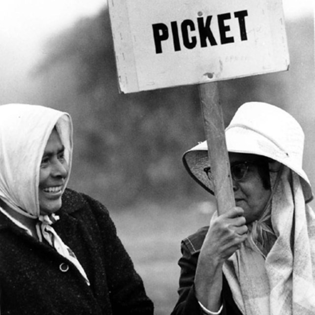 Two older women. One holds a labor protest sign.