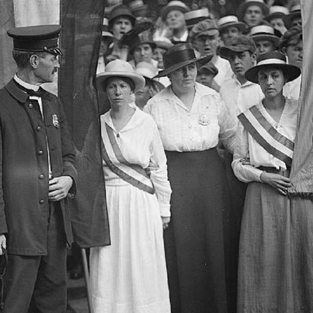 Group of suffragists picketing.