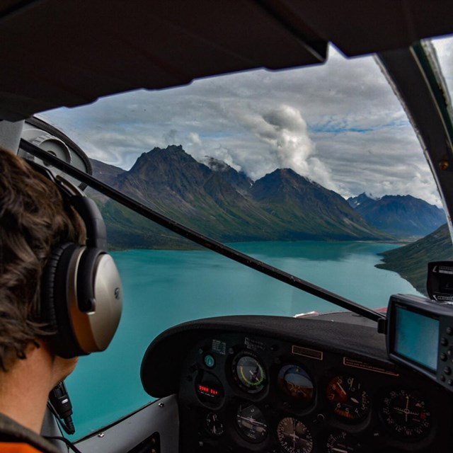 An NPS pilot looks out the cockpit window towards a turquoise lake