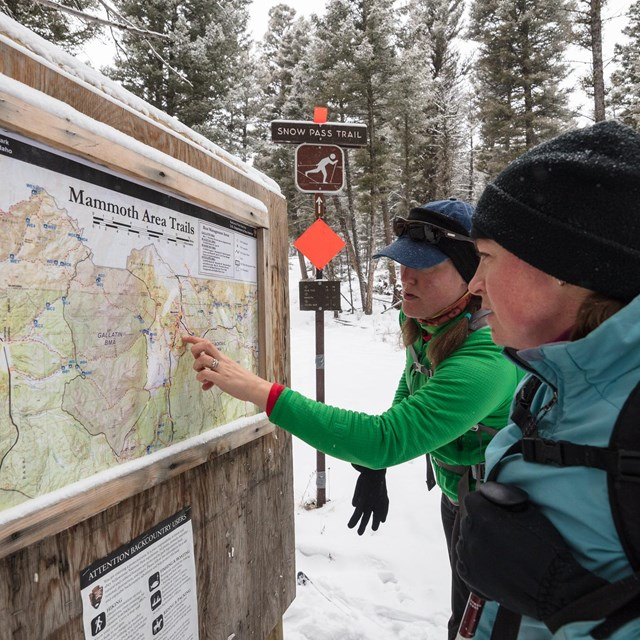 Two skiers reading a topo map on a bulletin board