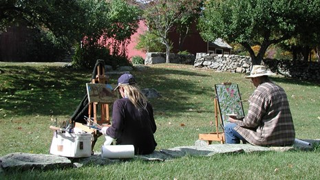two people sitting on a lawn, painting
