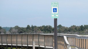 photo of handicapped access parking sign in front of wheelchair accessible boardwalk